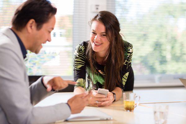 Vrouw lacht tijdens een meeting van een organisatieadviesbureau