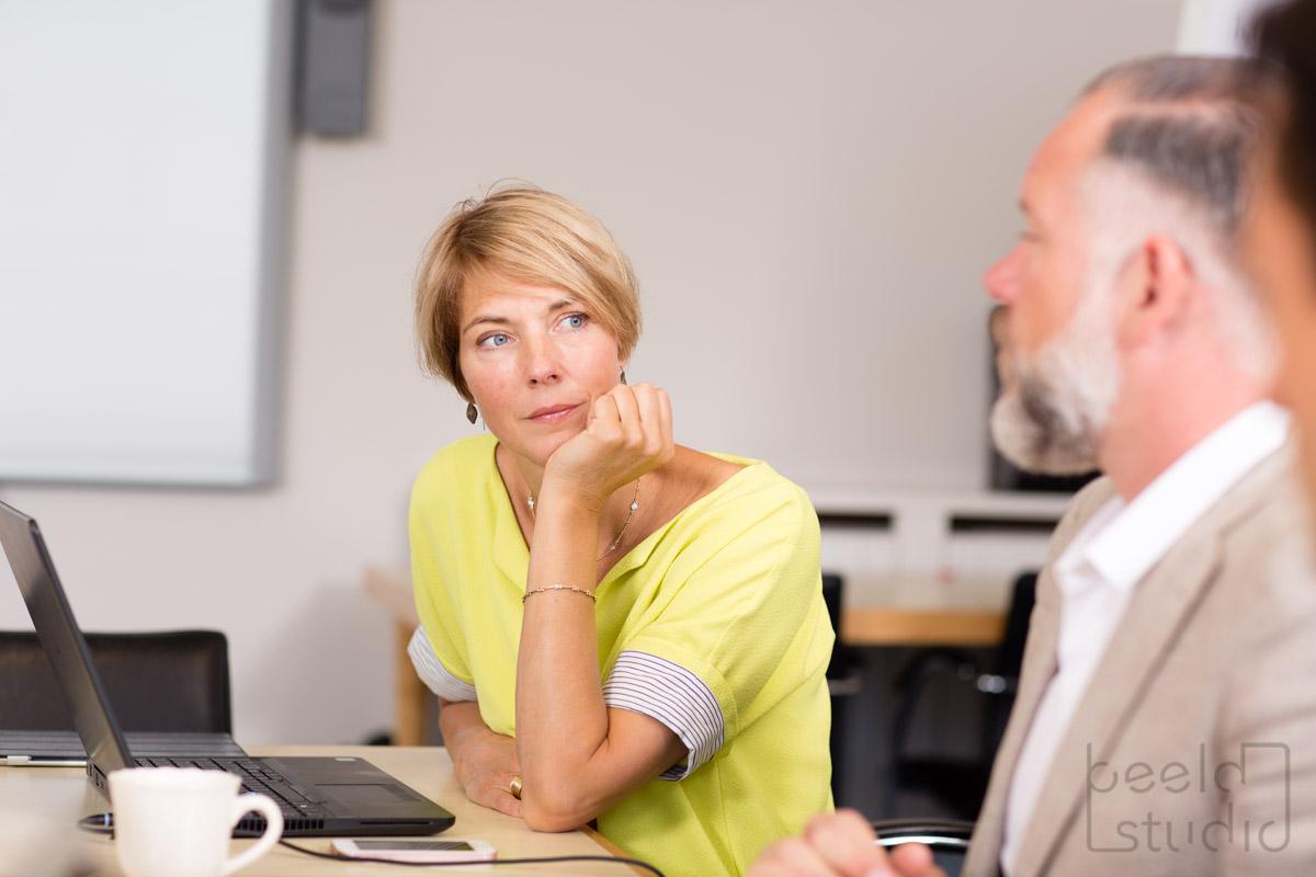 Vrouw kijkt bedachtzaam tijdens een vergadering van een organisatieadviesbureau