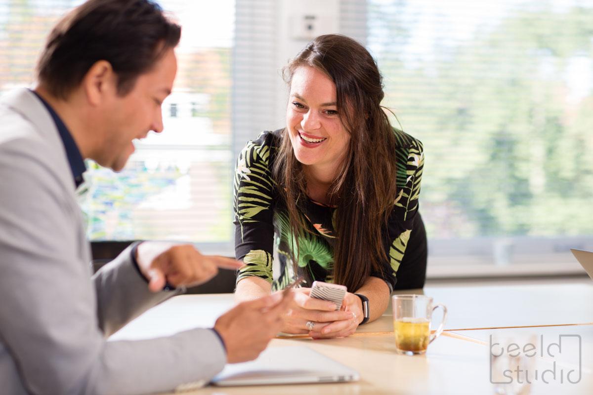 Vrouw lacht tijdens een vergadering van een organisatieadviesbureau