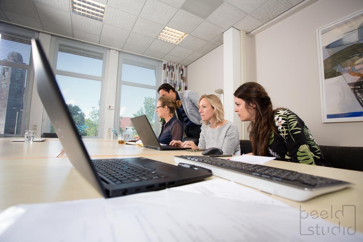 Collega's bekijken iets op de laptop tijdens een vergadering bij een organisatieadviesbureau
