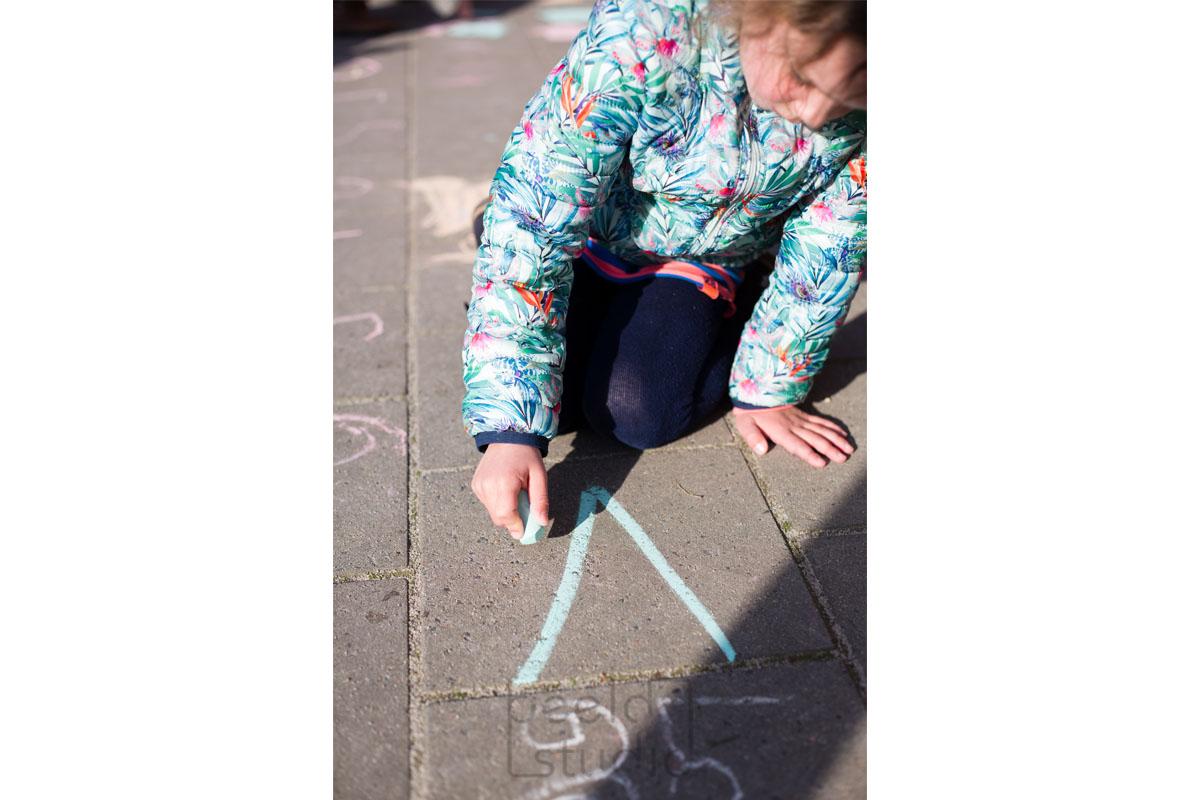 Meisje met krijt op het schoolplein van de kleuterschool