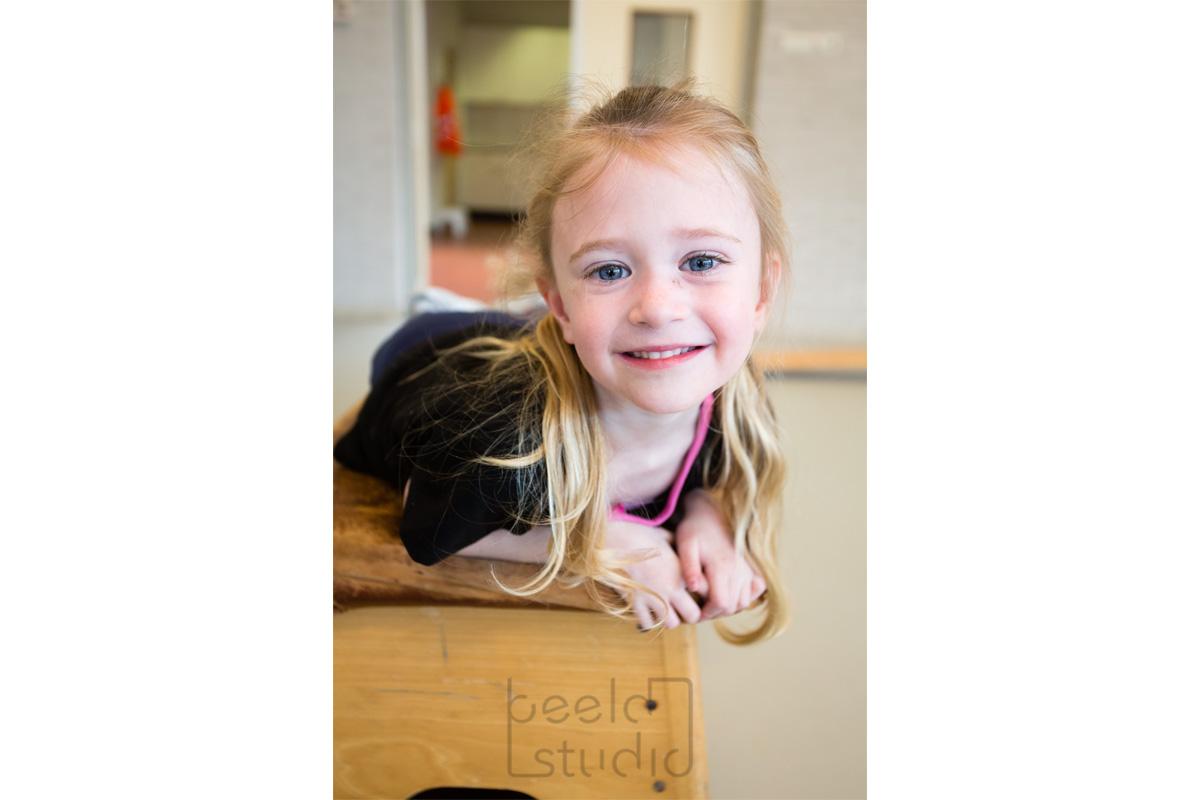 Lachend meisje in de gymzaal van een kleuterschool