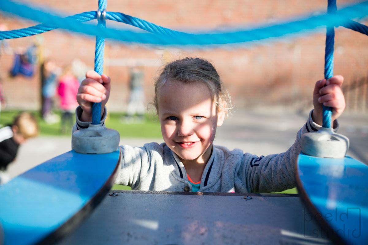 Meisje lacht op het schoolplein van de kleuterschool
