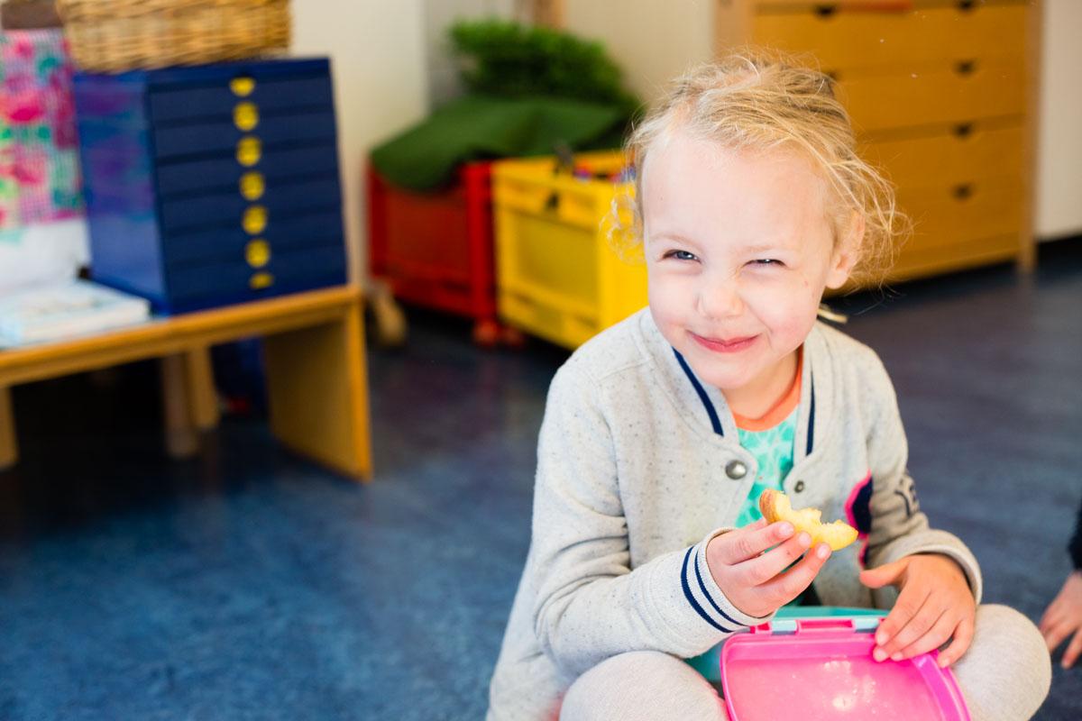 Meisje eet op een kleuterschool